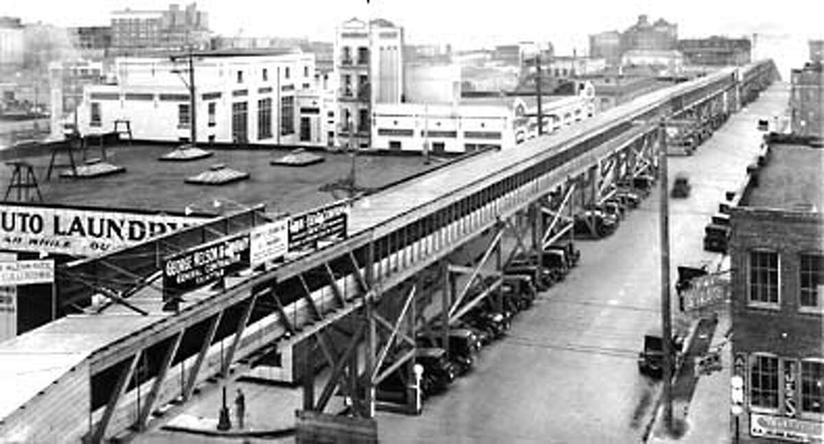 An overhead wooden gallery was built along Battery Street to support the conveyor belt carrying dirt from the regrade project toward Elliott Bay. The gallery was torn down after the project's completion. Photo circa 1930.
