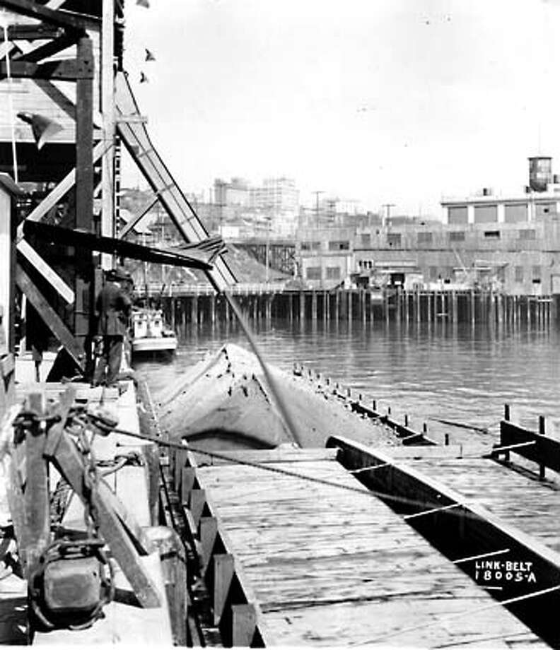At the waterfront, the dirt was loaded onto self-dumping barges. Photo circa 1930. Photo: Seattle Post-Intelligencer