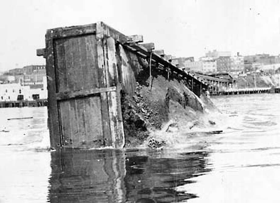The last stop for the remains of Denny Hill was at the bottom of Elliott Bay. This photo, taken around 1930, shows a scow dumping 600 cubic yards of dirt. Photo: Seattle Post-Intelligencer