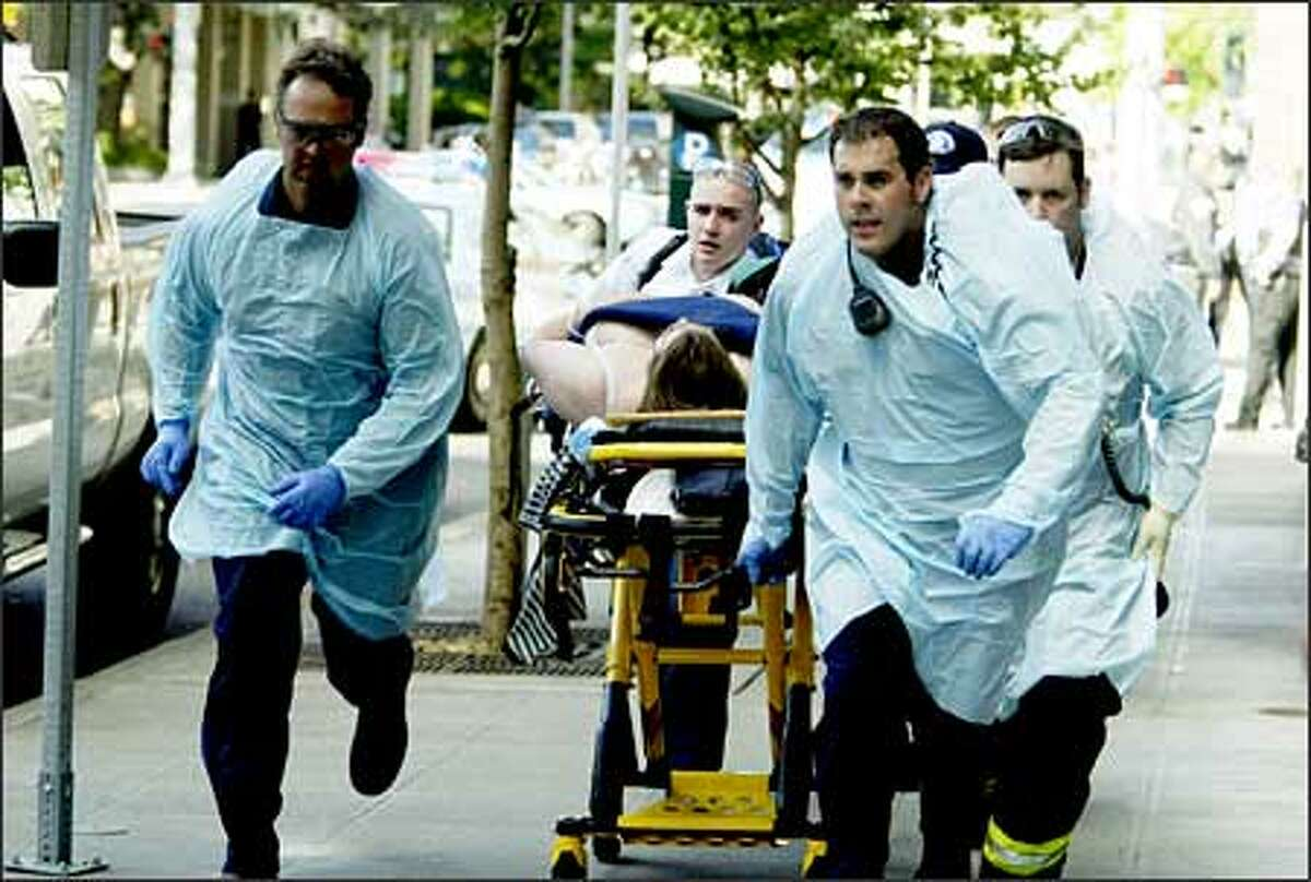 Paramedics rush away one of the six victims of a shooting at the Jewish Federation of Greater Seattle's offices downtown on Friday. One victim died, and five more -- all women -- were wounded.