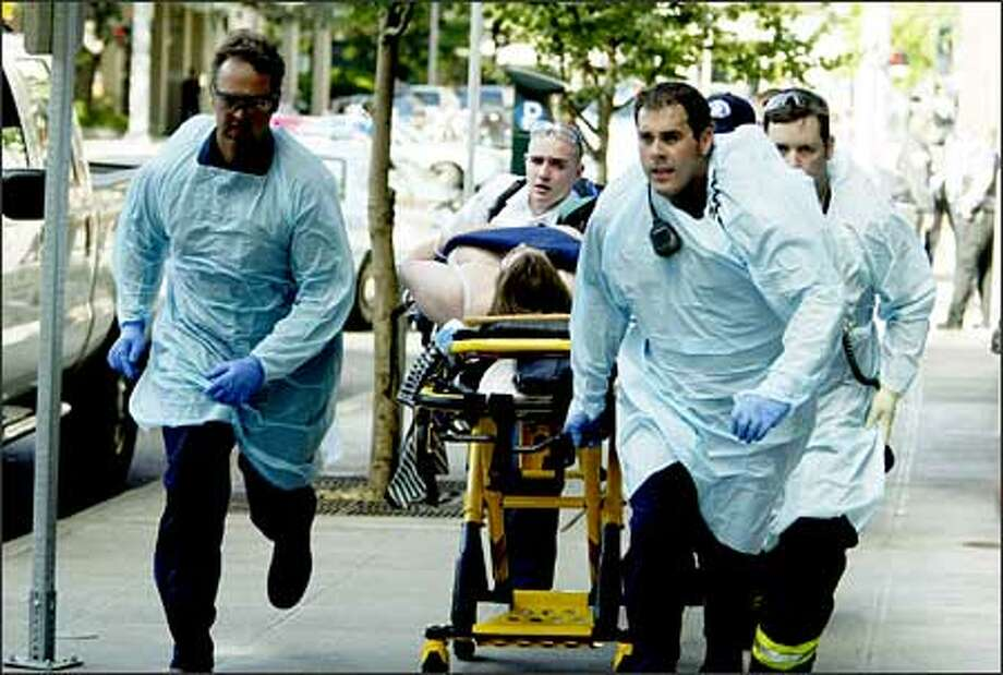 Paramedics rush away one of the six victims of a shooting at the Jewish Federation of Greater Seattle's offices downtown on Friday. One victim died, and five more -- all women -- were wounded. Photo: Mike Urban, Seattle Post-Intelligencer