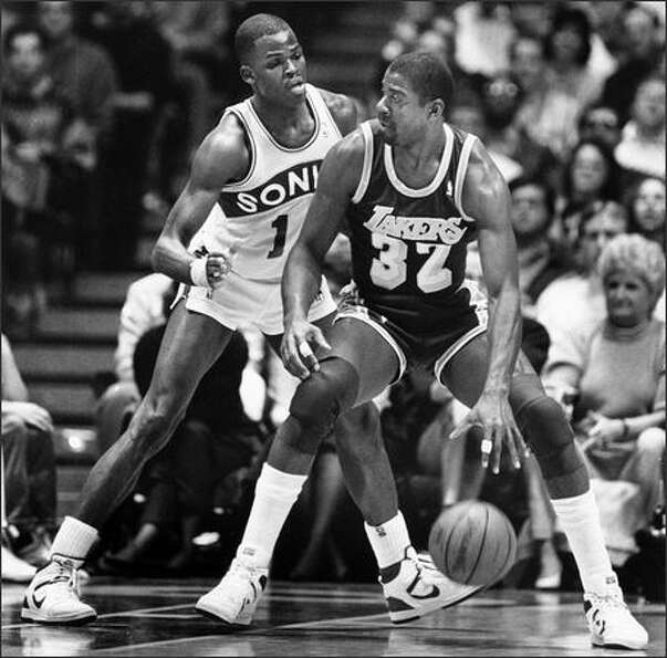 Nate McMillian of the Sonics tries to stop Magic Johnson of the Lakers at the Seattle Colliseum on J