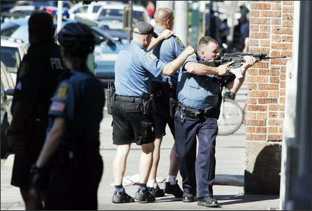 Police, uncertain of how many gunmen were involved, cover an alley near the Jewish Federation offices on Third Avenue.