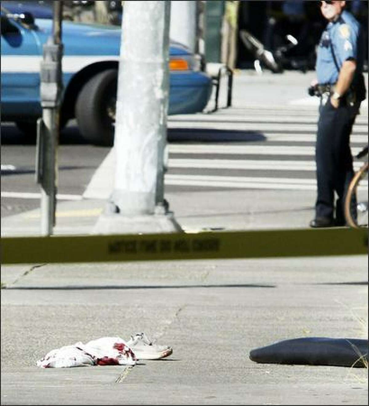 A police officer looks at evidence near the scene of the shootings in Belltown: a shoe and bloody clothing.