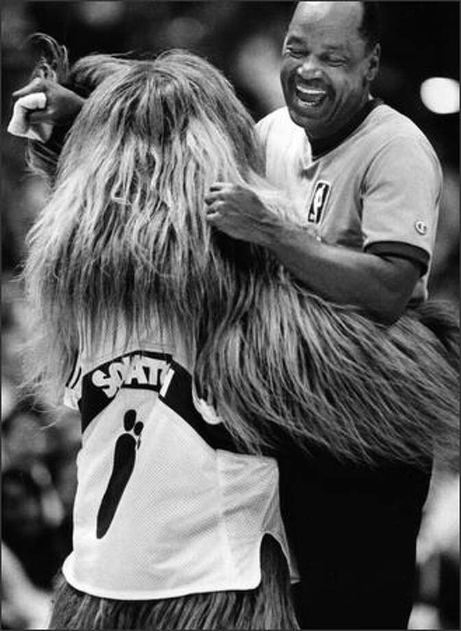 Squatch, the Sonics' mascot, gives a bear hug to NBA referee Hugh Evans. (P-I photo by Kurt Smith)