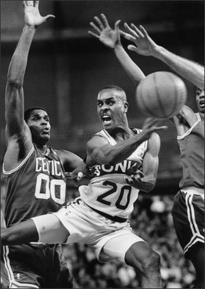 Gary Payton dishes off the ball in heavy traffic in front of Boston's Robert Parrish on Dec. 29, 1992. (P-I photo by Kurt Smith)
