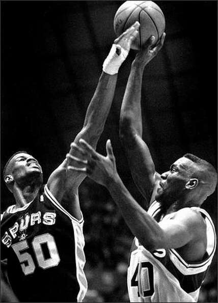 San Antonio's David Robinson tries to block a shot by the Sonics' Shawn Kemp on Jan. 27, 1993. Robin