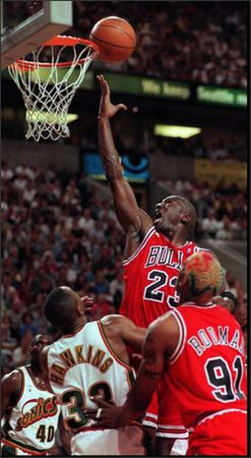 Michael JORDAN GOES FOR THE FINGER ROLL AGAINST SONIC DEFENDERS IN THE FIRST HALF in 1996 playoff game Photographer:MIKE URBAN