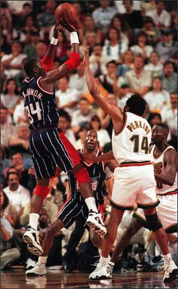 Hakeem Olajuwon shoots over Sam Perkins in the first half of Game 6 in NBA playoff series