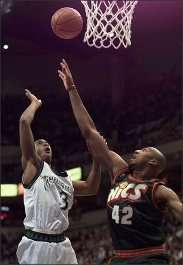 Seattle SuperSonics forward Vin Backer, right, reaches up to block a shot by Minnesota Timberwolves guard Stephon Marbury during the first quarter of game three of their NBA playoff game in Minneapolis, Tuesday April 28, 1998. (AP Photo/Charles Krupa)