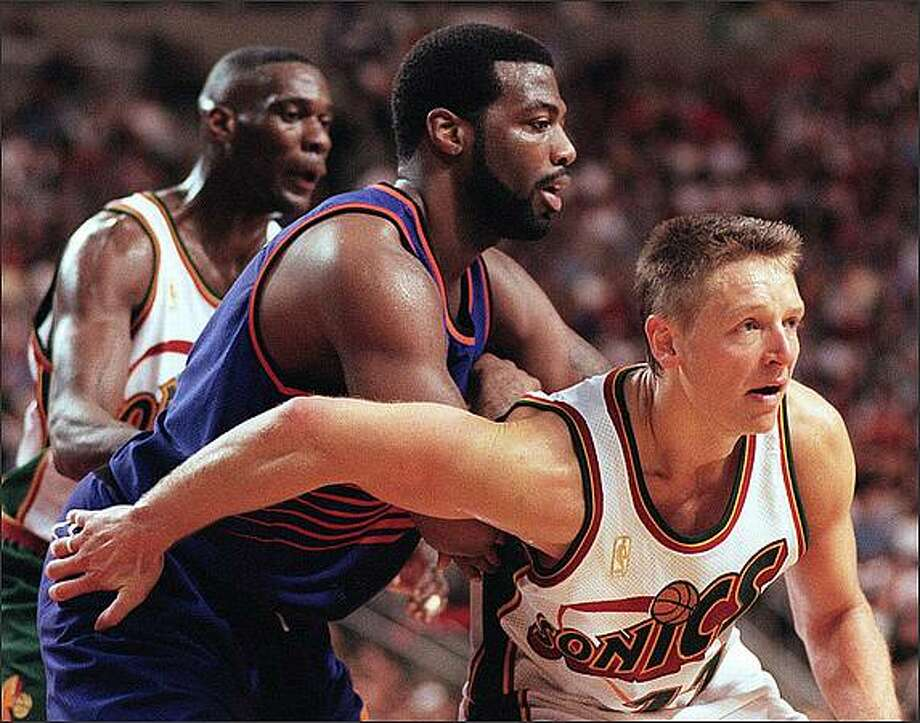Detlef Schrempf (right) reaches back to keep Phoenix Suns Danny Manning in place on May 3, 1997. At rear is Shawn Kemp. Photo by Grant M. Haller