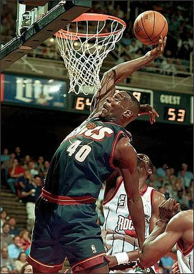 Shawn Kemp goes in for a dunk as Houston Rockets' Hakeem Olajuwon defends during the second quarter of their NBA playoff game Monday, May 5, 1997, in Houston. (AP Photo/Pat Sullivan)