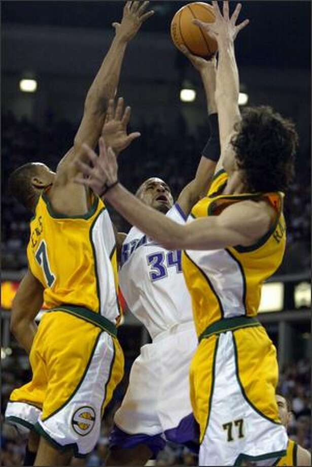 Rashad Lewis and Vladimir Radmanovic put up a block on Sacramento's Corliss Williamson during the playoff series in 2005. Photo: Gilbert W. Arias, Seattle Post-Intelligencer