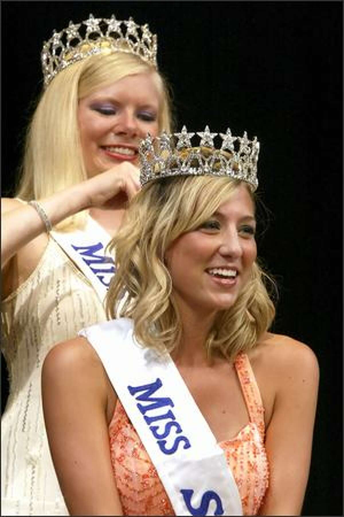 New Miss Seafair Erin Waid, front, is all smiles as she is crowned by former Seafair Queen Melissa Parks during the Coronation Tuesday in Seattle.