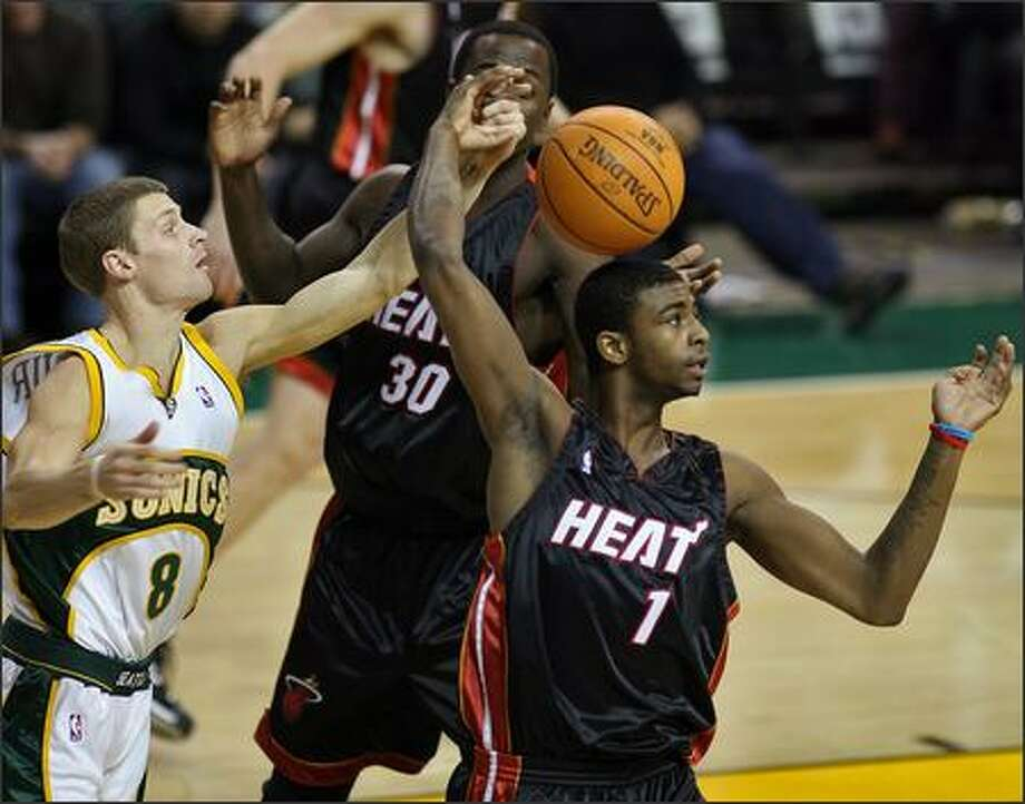 The Sonics' Luke Ridnour flicks the ball away from Miami's Dorell Wright during a game against the Heat in 2006-07. Photo: Mike Urban, Seattle Post-Intelligencer