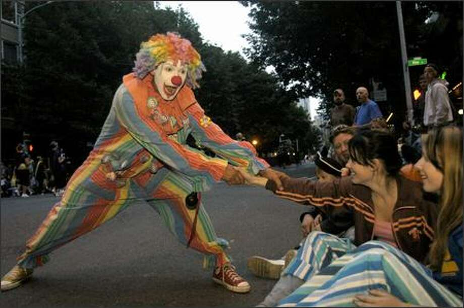 A Seafair clowns jokes with Amanda Smith, 13, during Saturday's Torchlight Parade. Photo: Julie Graber, Special To The Seattle Post-Intelligencer
