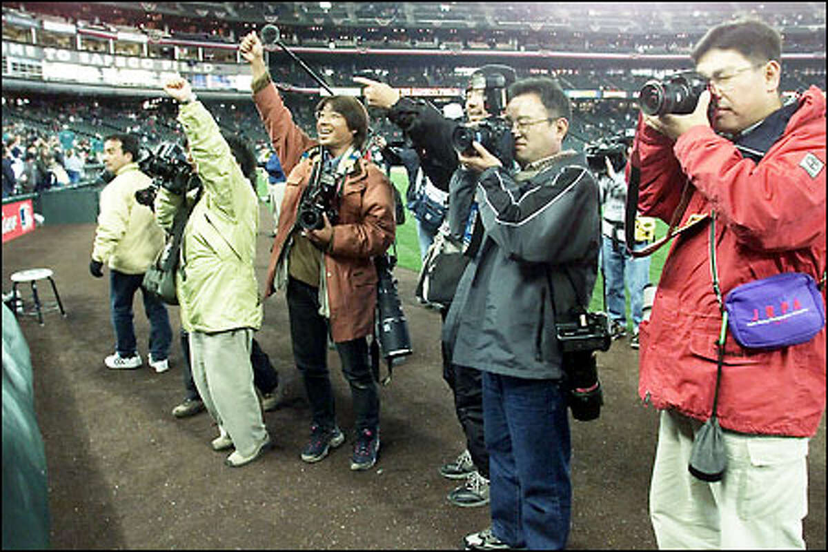 Japanese media members try to get Mariners fans to cheer for a photograph Monday at Safeco Field during the Mariners' home opening game.