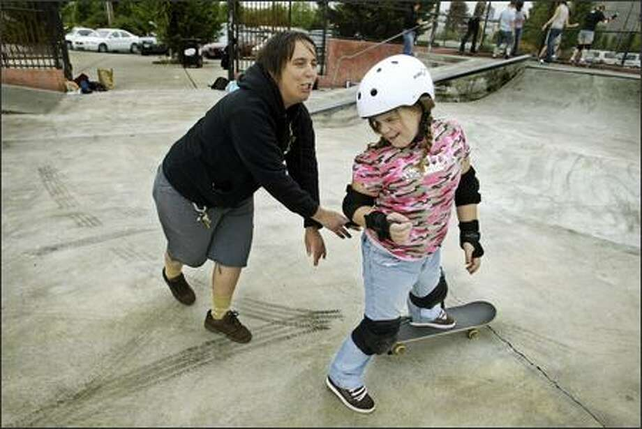 Skate Like a Girl co-founder and instructor Holly Sheehan, left, has some fun with Skylar Macklin during a free clinic at Seattle Center Skate Park last Wednesday. Photo: Gilbert W. Arias, Seattle Post-Intelligencer