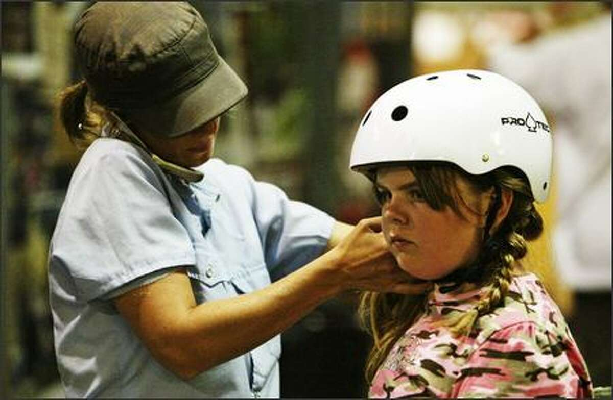 Fleur Larsen, left, who helped found Skate Like a Girl, adjusts 9-year-old Skylar Macklin's helmet during a clinic in Renton last Wednesday.