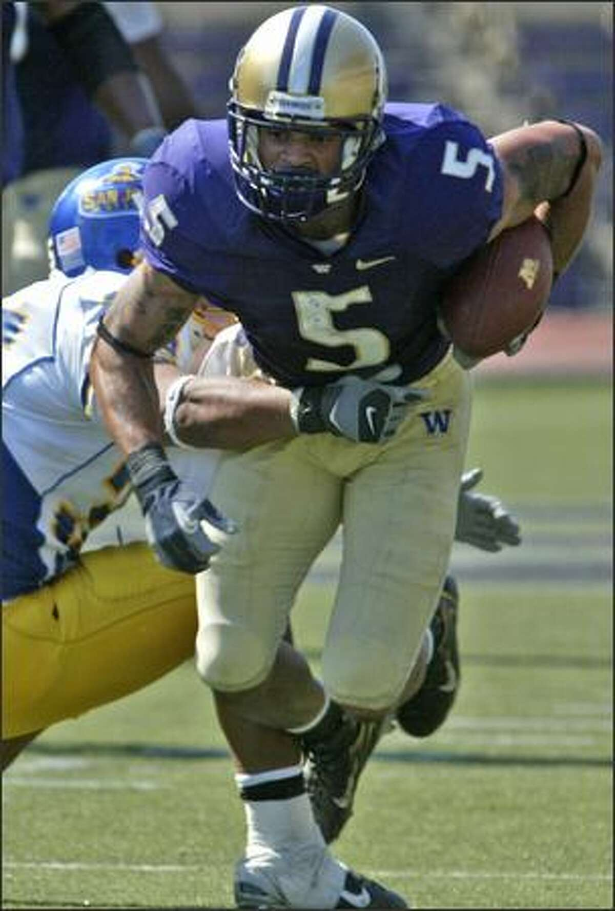 UW's Anthony Russo (5) runs for three yards with Spartans Matt Castelo reaching for him late in third quarter.
