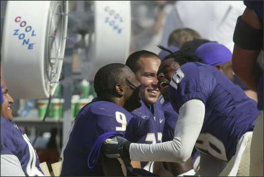 UW's Corey Williams (18) shakes his dreadlocks in Louis Rankin's face as they celebrate Rankin's 68-yard run to score a touchdown late in the fourth quarter.