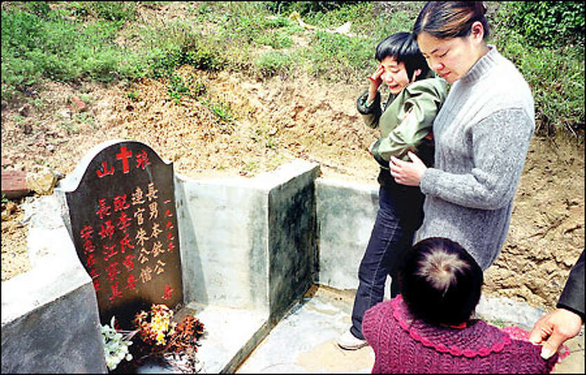 Jiang Saimei, left, weeps inconsolably at the hillside grave of her husband, Zhu Benqing, until her sister-in-law, Zhu Li Rong, pulls her away. Looking on is Jiang's 3-year-old daughter, Zhu Shiyao. Zhu Benqi