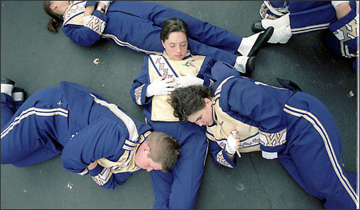 Members of the University of Washington marching band take a moment to rest before the game.