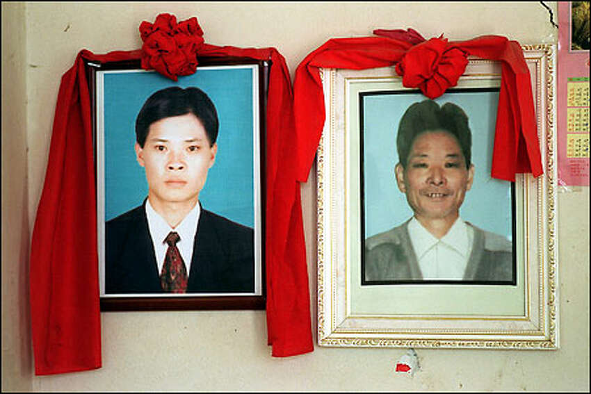 A portrait of Zhu Benqing hangs on the wall of his family's home, next to a portrait of his father, on the Chinese island of Langqi. Zhu wanted to join his brother-in-law in America.