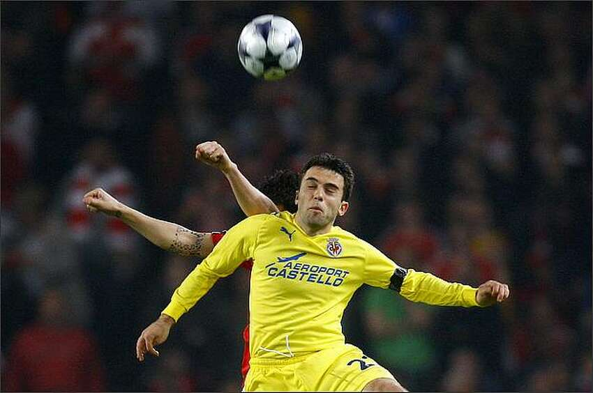 Arsenal's Cesc Fabregas, left, challenges Villarreal's Giuseppe Rossi during their Champions League quarter-final second-leg soccer match at the Emirates stadium in London on April 15.