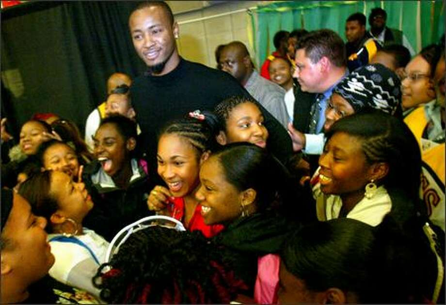 Seattle SuperSonics player Rashard Lewis is swarmed by teenagers after he appeared at Cleveland High School in West Seattle on Friday. Ray Allen and Rashard Lewis will be replacing the boys basketball team's equipment at Cleveland High School, which was stolen earlier this month. Allen's Ray of Hope Foundation and Lewis' Rashard Lewis Foundation, along with the Sonics and Storm Foundation, will also present the school with a monetary donation to help the basketball team this season. Photo: Karen Ducey, Seattle Post-Intelligencer