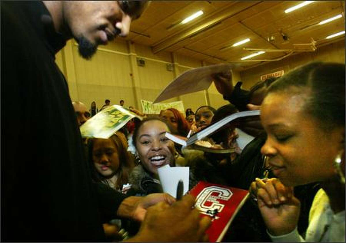 Sonics player Rashard Lewis is swarmed by teenagers including Azieb Berhane, 17, right, as he signs autographs after he appeared at Cleveland High School in West Seattle on Friday.