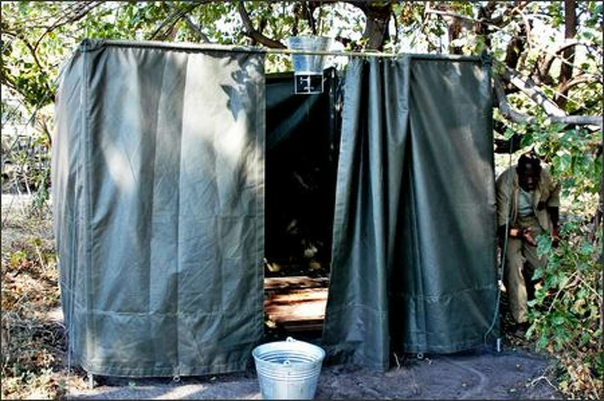 A bucket shower tent. A camp staffer fills the container with hot water, then raises or lowers it to match your height.