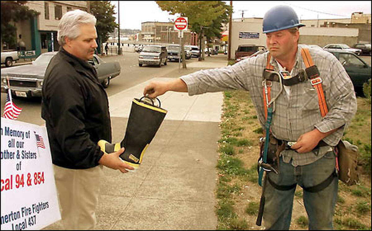 A construction worker drops a donation into a firefighter's boot held by Bremerton Fire Marshal Scott Rappleye. The money will be given to the families of New York firefighters killed in the collapse of the World Trade Center.