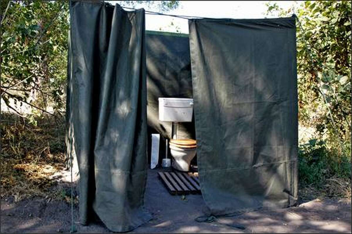 A toilet tent, with a flush toilet fed by a water container in the back.