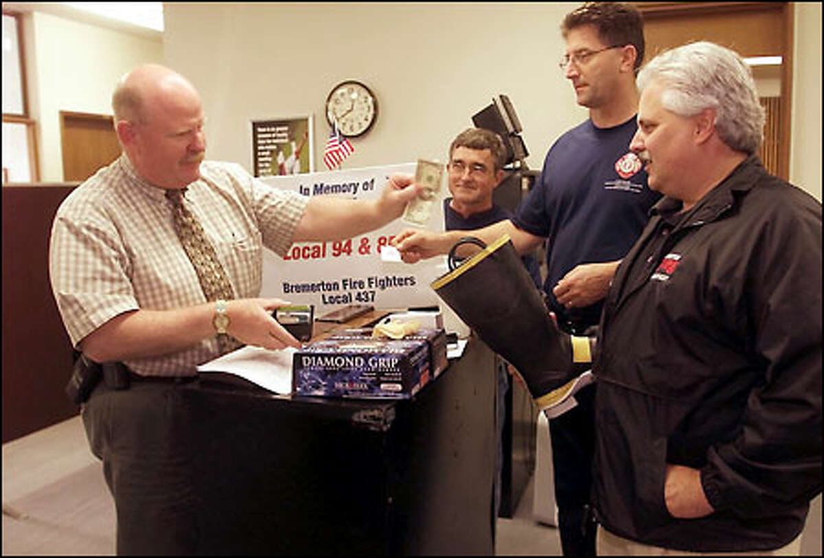 Bremerton police Detective Oakley donates money to a fund for the families of the New York firefighters killed in the collapse of the World Trade Center. Bremerton firefighters Dan Siegner, Jim McCall and Scott Rappleye solicited the donations from all over downtown.