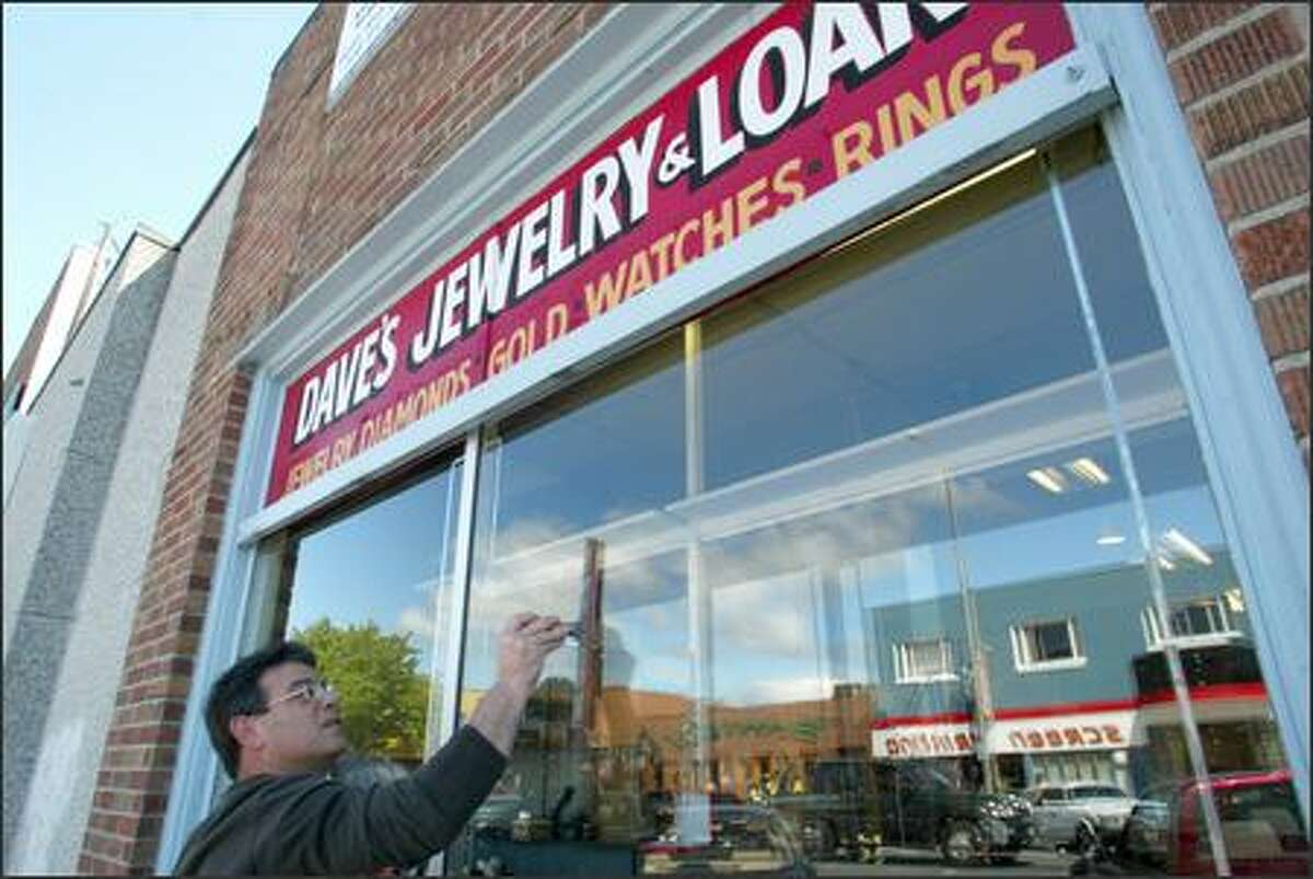 Dave Reibman cleans the storefront window of his store, Dave's Jewelry and Loan, on 16th Avenue Southwest in White Center on May 20. Reibman would like White Center to remain unincorporated.