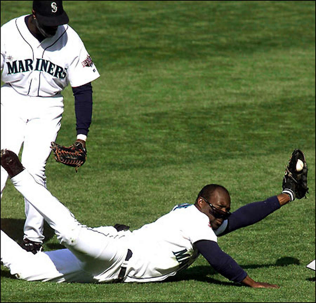 Mariners shortstop Mark McLemore makes a diving catch for a blooper by Cleveland's Juan Gonzalez in the second inning. Center fielder Mike Cameron looks on.