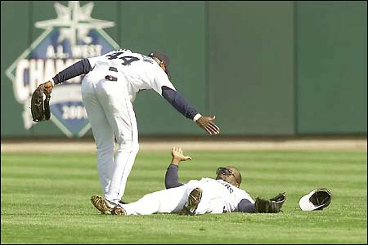 Center fielder Mike Cameron offers shortstop Mark McLemore a hand up after McLemore made a diving catch in the second.