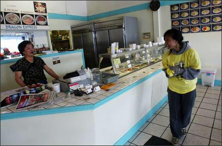 Volunteer Vesna Danh (right) speaks with Yon Hok, owner of the Dragon Express restaurant.