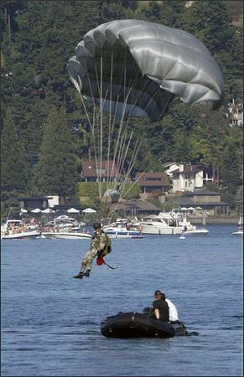 A U.S. Air Force combat controller makes a water landing after jumping from a transport plane over Lake Washington.