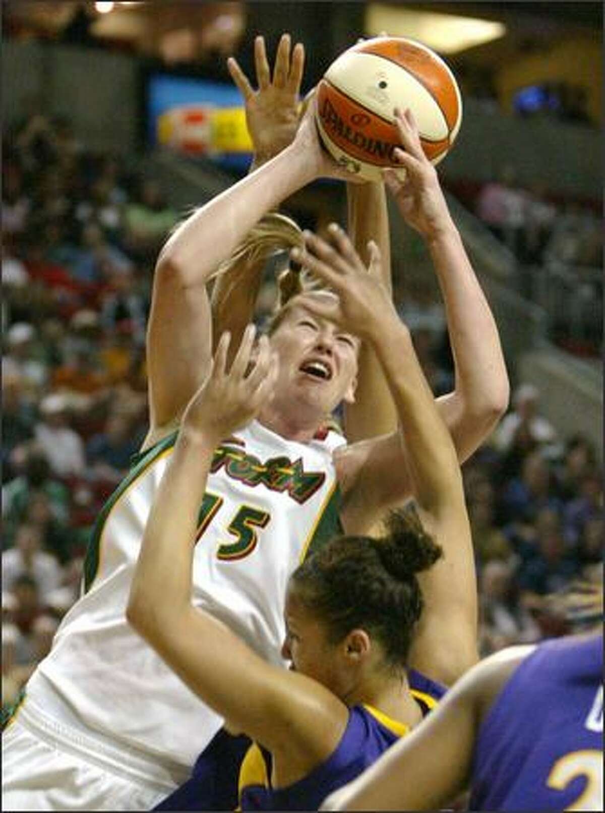The Storm's Lauren Jackson is fouled by the Sparks' Lisa Leslie on Sunday at KeyArena. Jackson led Seattle with 23 points.