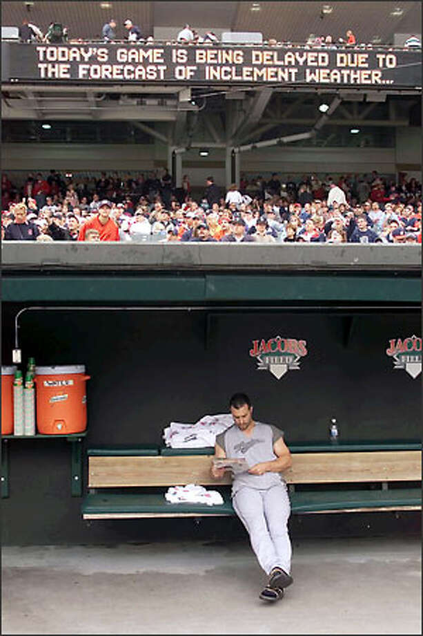 Mariner Tom Lampkin sits in the visitors' dugout reading Parade magazine as a reader board in Cleveland's Jacobs Field announces a rain delay for Sunday's game -- which finally started two hours and 20 minutes late. Photo: Mike Urban, Seattle Post-Intelligencer