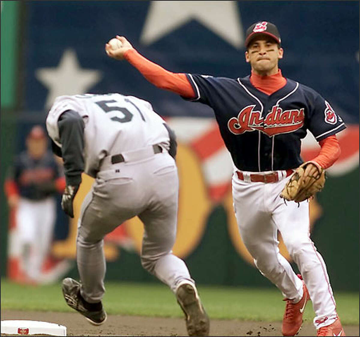 Ichiro ducks but is out at second as Cleveland shortstop Omar Vizquel turns the double play in the first inning of play.