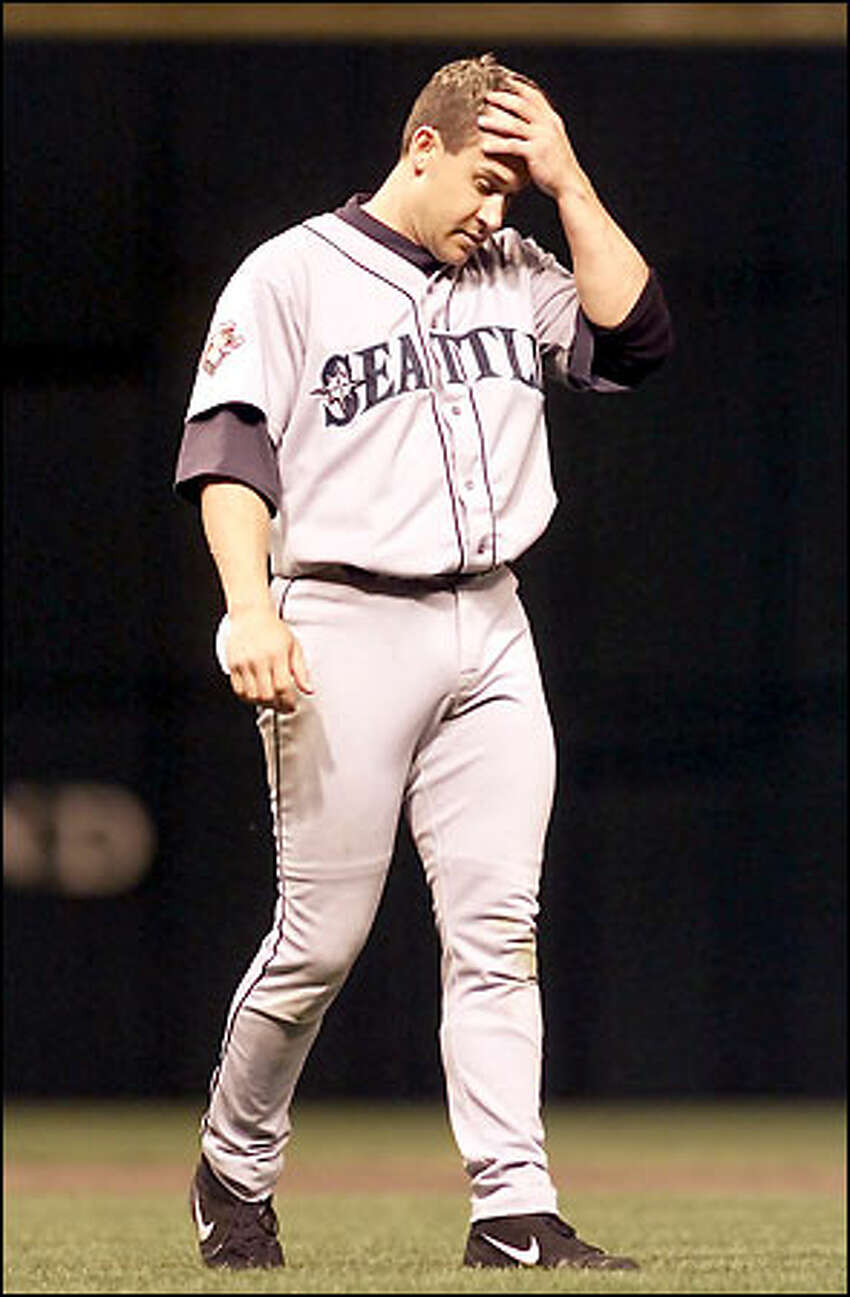 Bret Boone, who struck out swinging four times in his five at-bats, walks back to his position on the field after ending an inning.
