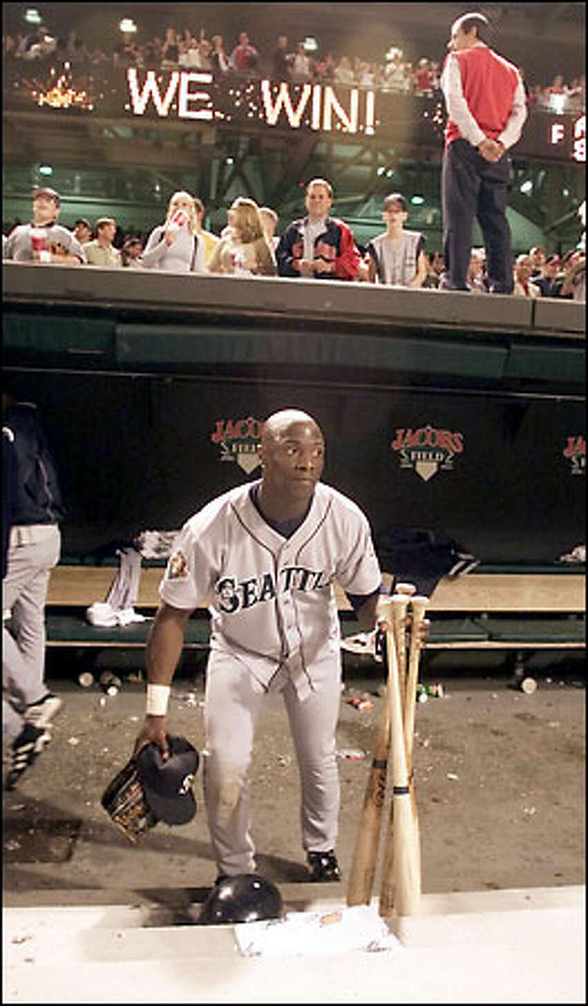 Mike Cameron picks up his bats, glove and hat from the dugout after the Mariners' 17-2 loss to the Cleveland Indians.