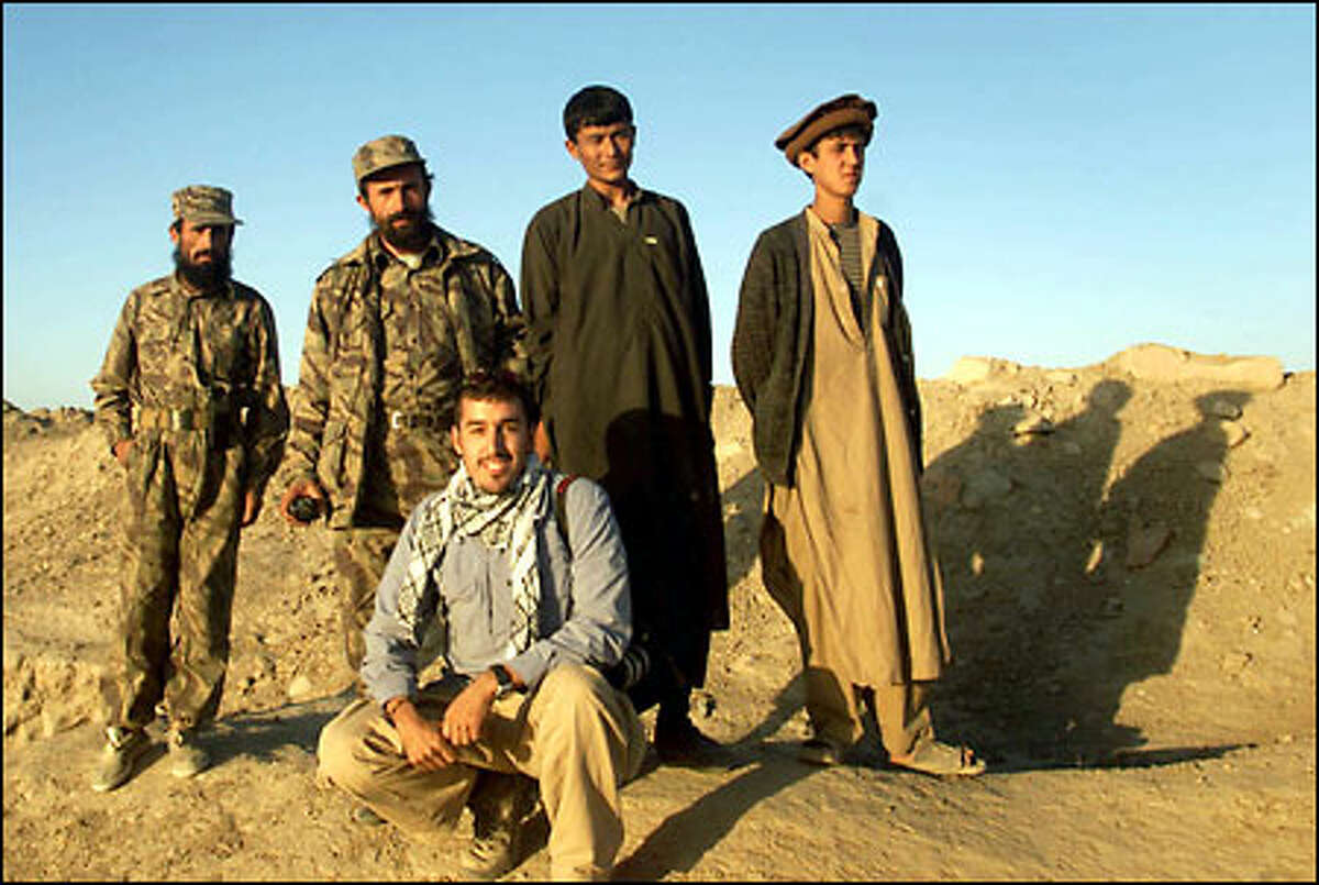 P-I photographer Joshua Trujillo poses with a group of rebels in Afghanistan.