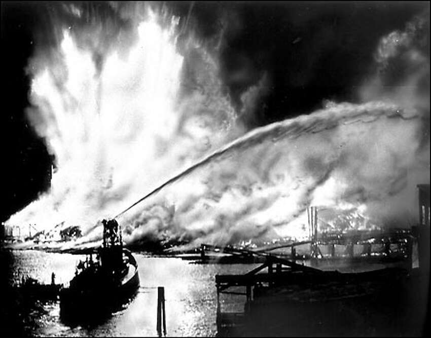 Seattle Cedar mill fire, 1958: On May 20, 1958, a massive fire destroyed the Seattle Cedar Lumber Manufacturing Co. at Salmon Bay in Ballard. The blaze, the largest in Seattle since the fire of 1889, started when sawdust ignited next to steam pipes. Fireboats poured water on the flames, which leaped hundreds of feet into the air in the kiln and storage area. Heat from the fire was felt more than two blocks away. The company, founded in the 1890s, was rebuilt and regained peak production a year later. P-I photographer Phil H. Webber shot this picture from the Ballard Bridge.