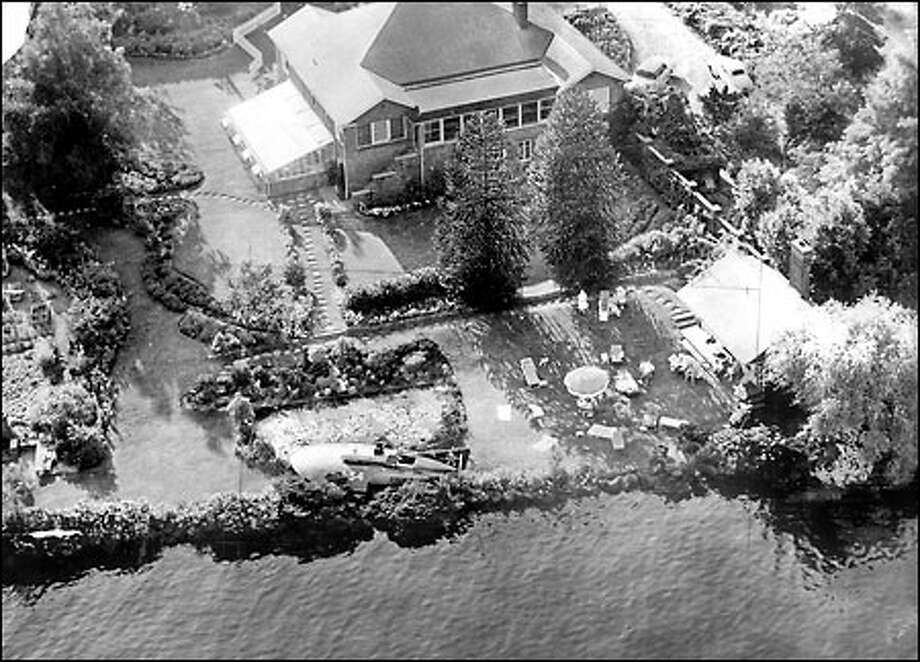 1954 Seafair Gold Cup: The hydroplane Gale IV, bottom center, came to rest in the front yard of Dr. F.A. Black, 1500 Lakeside Ave. S. after an Aug. 8 mishap during a heat of the 1954 Gold Cup race on Lake Washington. Onlookers in the yard were startled but uninjured when the boat roared ashore. Photo: Seattle Post-Intelligencer