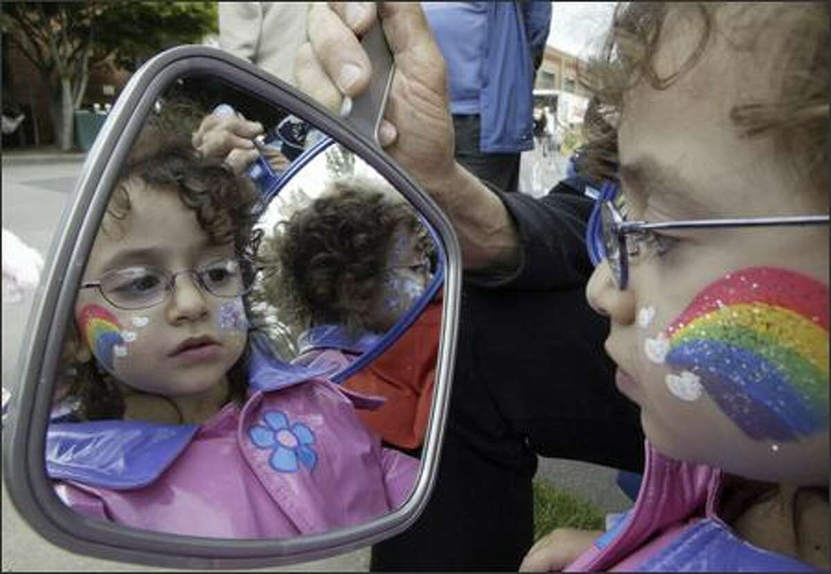 Harriet Simons examines her newly painted face in a mirror during the Fremont Fair.