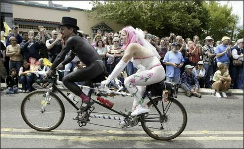 Painted up as newlyweds, a couple rides tandem in the 18th annual Summer Solstice Parade in Fremont. One of the parade's highlights is the procession of cyclists sporting nothing but body paint.